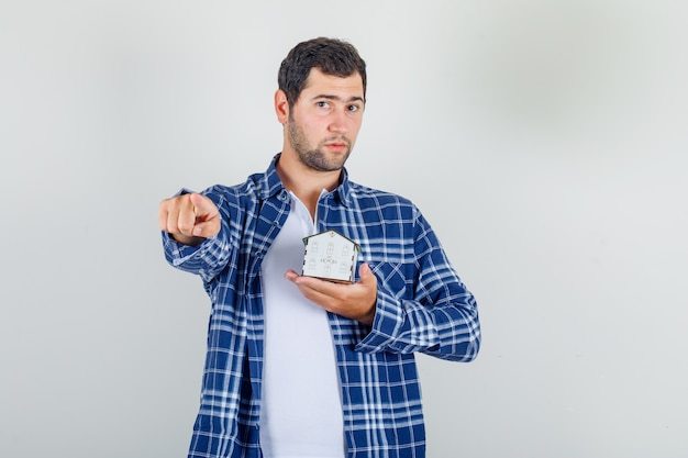 Young man pointing finger to front with house model in shirt