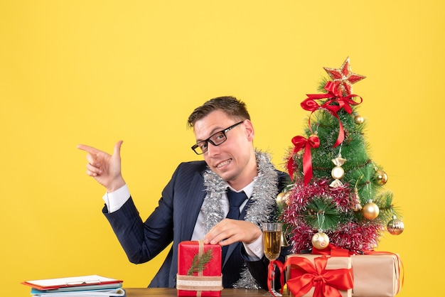 Young man pointing finger something sitting at the table near xmas tree and presents on yellow