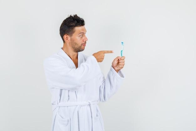Giovane uomo puntare il dito allo spazzolino da denti in accappatoio bianco, vista frontale.