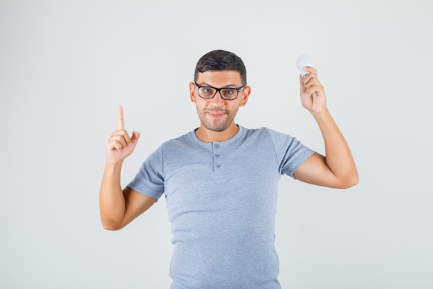 Young man pointing finger up and holding light bulb in grey t-shirt, glasses front view.
