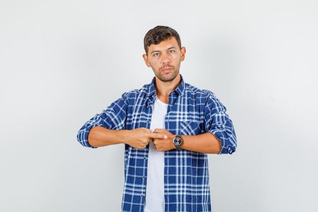 Giovane uomo che punta il dito all'orologio in camicia e guardando serio, vista frontale.
