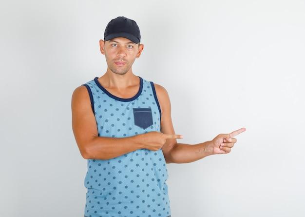 キャップと青い一重項で離れて指を指している若い男