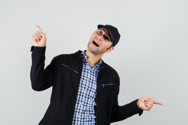 Молодой человек указывая пальцами в рубашке, куртке, кепке и выглядит весело. передний план.