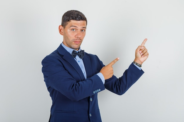 Young man pointing fingers away in suit and looking careful.