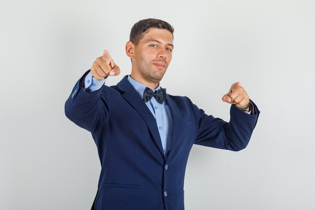 Young man pointing fingers to camera in suit and looking cheerful.