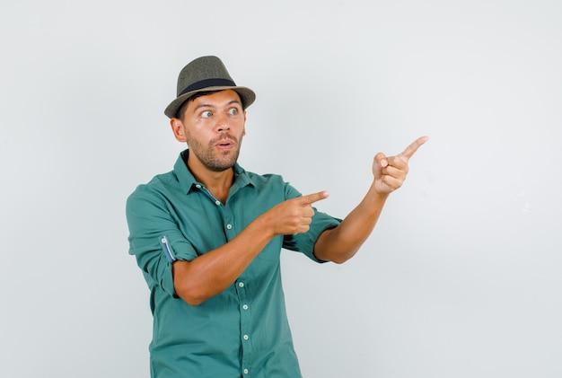 Молодой человек указывая пальцами в сторону в рубашке, шляпе и любопытно.