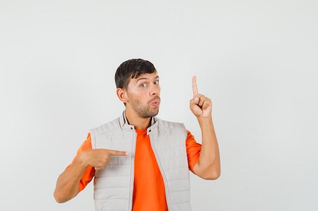 Молодой человек указывая пальцами вверх и в сторону в футболке, куртке и выглядит любопытно. передний план.