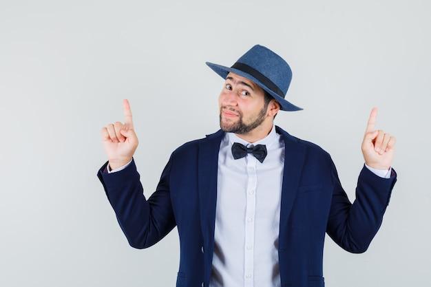 Молодой человек указывая пальцами вверх в костюме, шляпе и выглядит веселым, вид спереди.