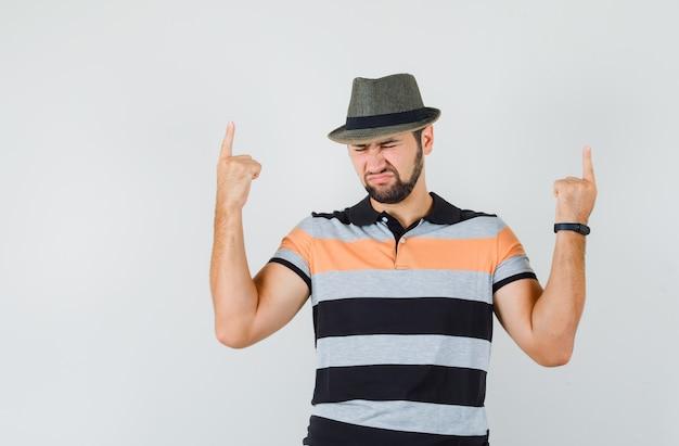若い男は、tシャツ、帽子、絶望的な、正面図で指を指しています。