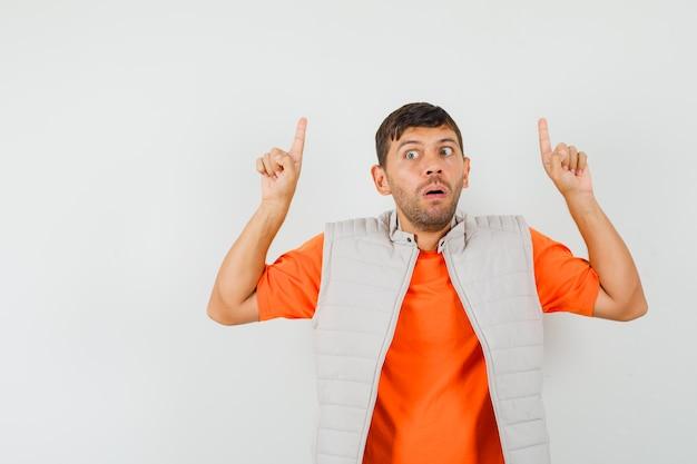 若い男はtシャツ、ジャケットで指を上に向けて怖がって見える