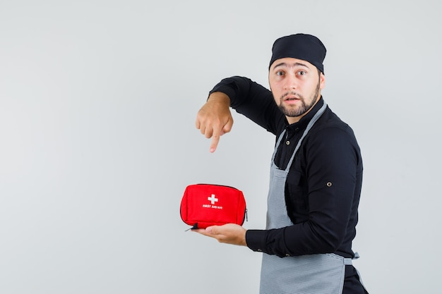 Young man pointing at first aid kit in shirt, apron and looking excited. front view.