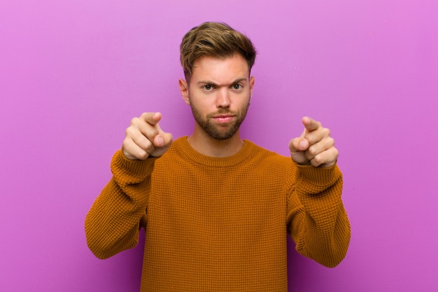 Young man pointing forward at camera with both fingers and angry expression, telling you to do your duty against purple wall