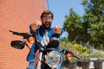 Young man pointing front on a motorbike