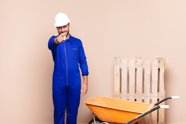 Young man pointing at front with a satisfied, confident, friendly smile, choosing you construction concept