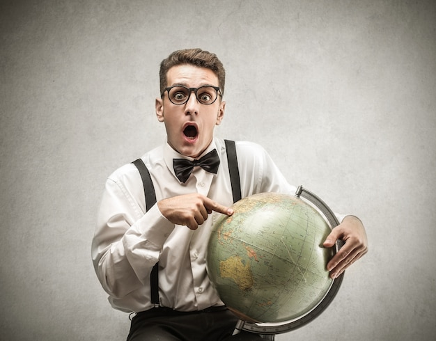 Young man pointing on a globe