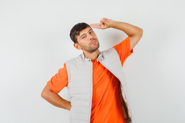 Tシャツ、ジャケット、自信を持って頭に手と指を指している若い男