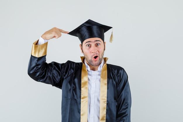 Giovane uomo che punta al suo berretto nero in uniforme laureato e guardando stupito, vista frontale.