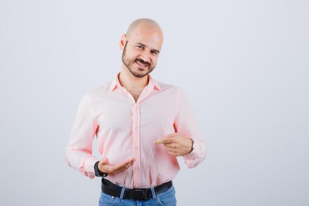 Giovane che indica la sua mano in camicia rosa, jeans, vista frontale.