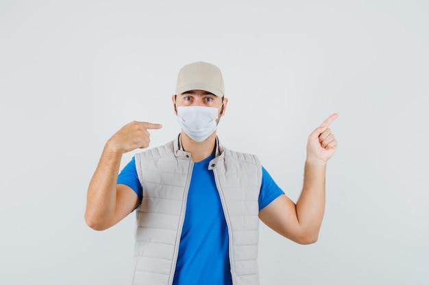 Giovane che indica la sua maschera e su in t-shirt, giacca, berretto e sembra serio, vista frontale.
