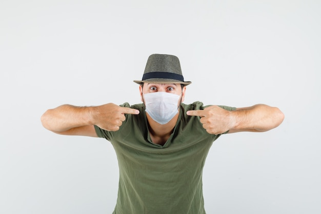 Young man pointing at his medical mask in green t-shirt and hat