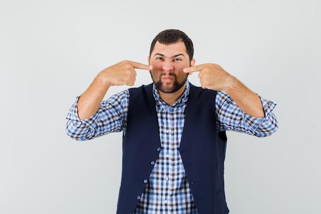 Giovane uomo che punta al naso mentre accigliato in camicia, giubbotto, vista frontale