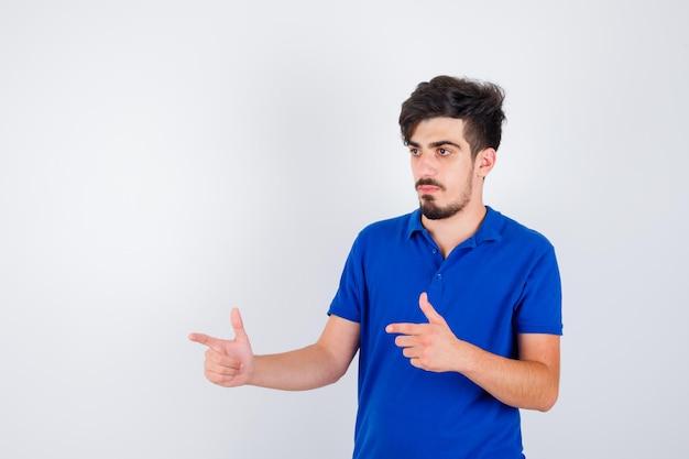 青いtシャツの人差し指で左を指して真剣に見える若い男