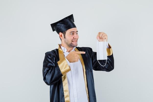 Giovane che indica alla mascherina medica in uniforme laureato e che sembra positivo. vista frontale.