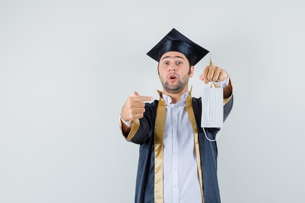 Giovane che indica alla mascherina medica in uniforme laureato e che sembra sorpreso, vista frontale.