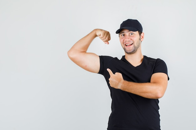 Young man pointing at muscle in black t-shirt, cap and looking cheerful