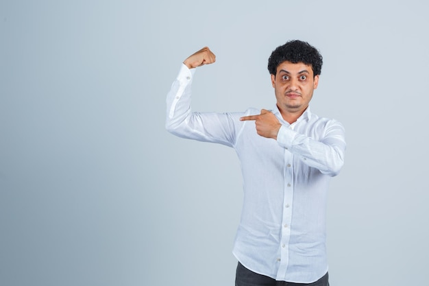 Young man pointing at muscles of arm in white shirt, pants and looking proud. front view.