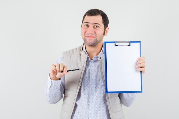Giovane che punta al taccuino con la penna in giacca beige e sembra ottimista, vista frontale.