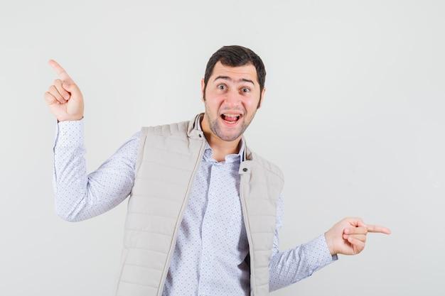 ベージュのジャケットの人差し指で反対方向を指し、楽観的に見える若い男。正面図。