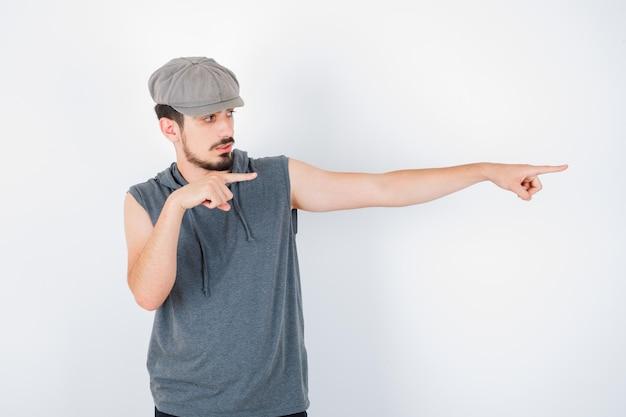 회색 티셔츠와 모자에 검지 손가락으로 오른쪽을 가리키고 심각한 찾고 젊은 남자