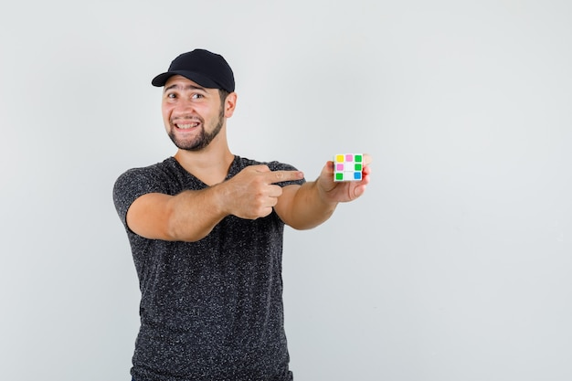 Young man pointing at rubik's cube in t-shirt and cap and looking cheery