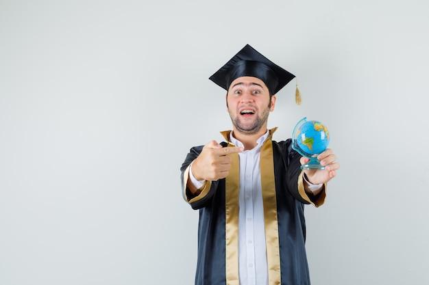Giovane che indica al globo della scuola in uniforme laureato e che sembra gioioso. vista frontale.