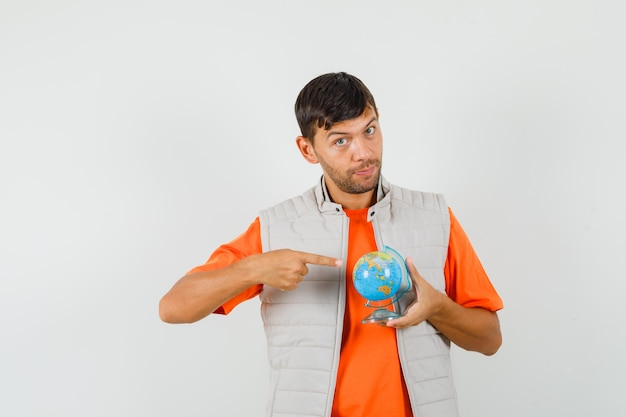 Young man pointing at school globe in t-shirt, jacket front view.