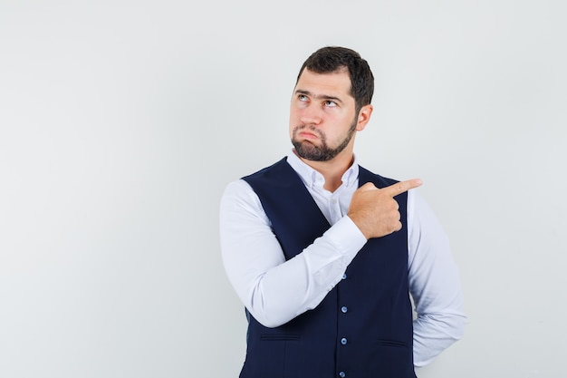 Young man pointing to side in shirt, vest and looking pensive