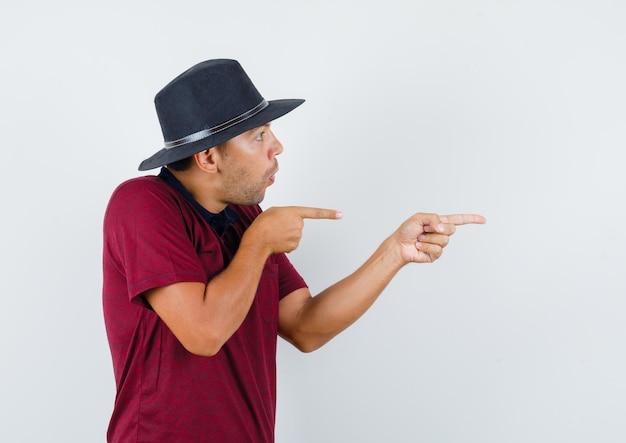 Giovane che punta al lato in maglietta, cappello e sembra domandato. vista frontale.