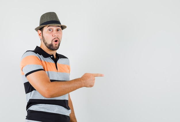 Young man pointing to the side in t-shirt, hat and looking wondered