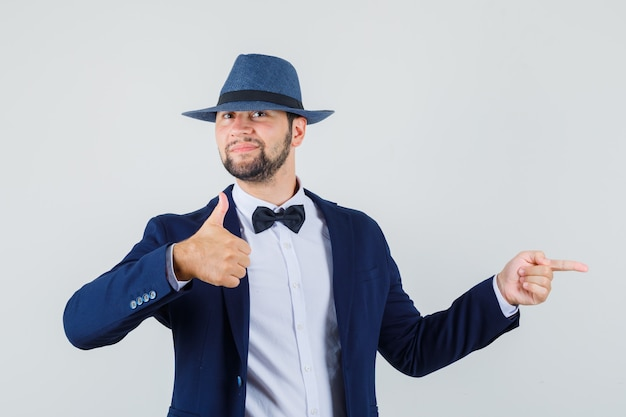 Young man pointing to the side with thumb up in suit, hat and looking pleased , front view.