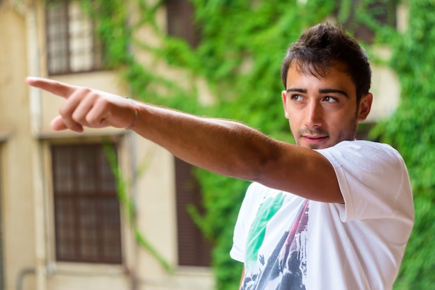Young man pointing something against green background