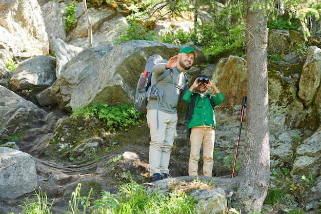 Young man pointing at something and telling about this wild place to the boy who looking through the binoculars while they standing on the hill