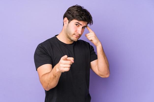 Молодой человек указывая пальцем висок, думая, сосредоточился на задаче.