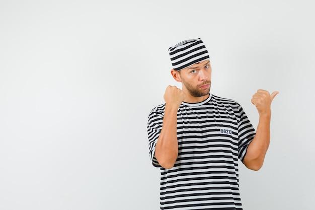 Giovane che indica il pollice lontano mostrando il pugno in cappello della maglietta a strisce e che sembra serio