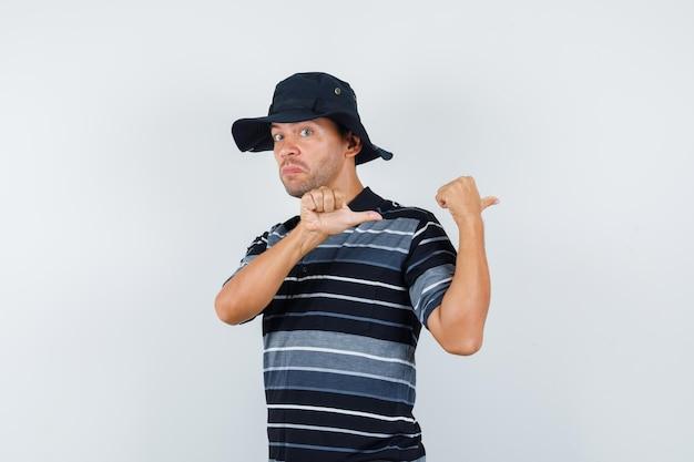 Молодой человек, указывая большими пальцами назад в футболке, шляпе и глядя нерешительно, вид спереди.