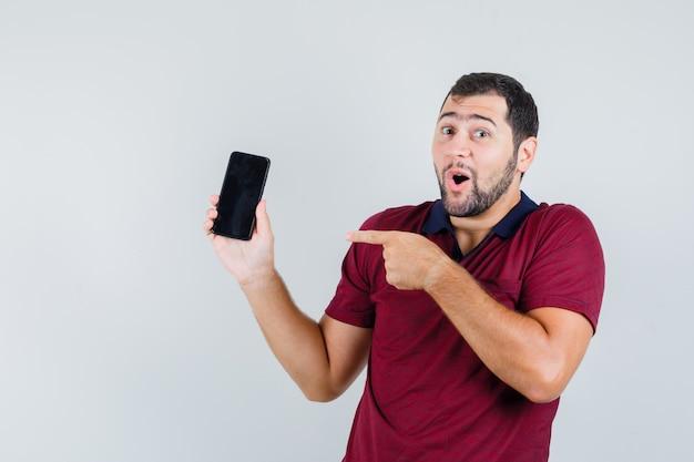 젊은 남자 빨간 티셔츠에 전화를 가리키고 놀라게, 전면보기를 찾고.