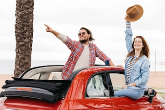 Young man pointing to side near woman waving hand with hat and leaning out from car
