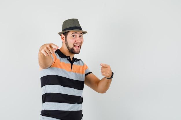 Tシャツ、帽子、陽気に見える前を指している若い男