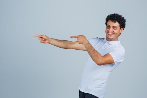 흰색 티셔츠를 입은 왼쪽을 가리키고 쾌활한 표정을 짓고 있는 젊은 남자.