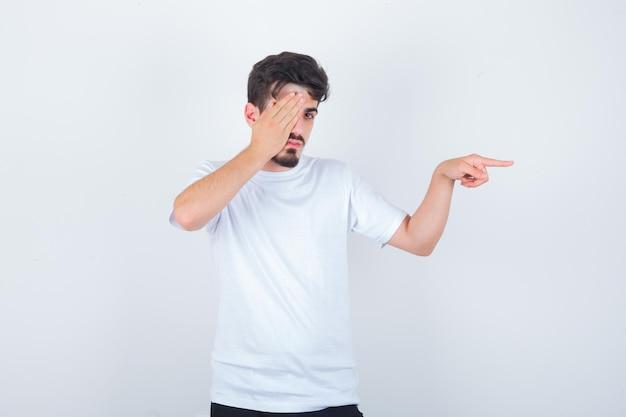 Tシャツで目を覆い、自信を持って見ながら右側を指している若い男
